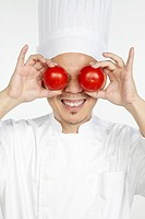 Asian chef holding tomatoes in front of eyes