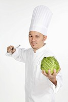 Asian chef with knife and cabbage in hand