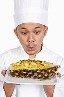 Asian chef with a plate of Thai pineapple fried rice