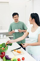 Woman cutting vegetables while man is drinking coffee
