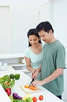 Woman teaching man to cut vegetables