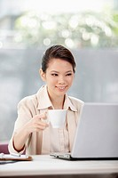 Businesswoman working on laptop while drinking beverage