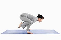 Businesswoman doing yoga crane pose
