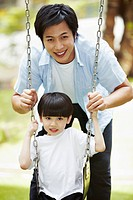 Father pushing son on the swing