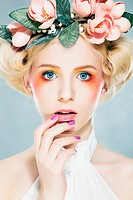 Beautiful blonde supermodel in wreath of flowers studio shot