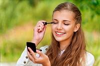 smiling cute woman paints eyelashes
