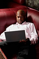African guy with laptop on sofa