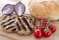 grilled meatballs whit cherry tomatoes, bread and red onions on wooden platter