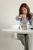 Businesswoman feeding goldfish