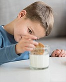 Boy (4-5) dipping cookie in milk