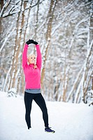 Woman exercising in winter forest
