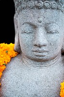 Stone Buddha statue with flowers