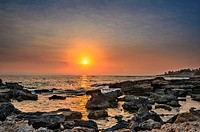 Sunset over the sea with stones on foreground