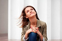 Happy young woman against a white wall