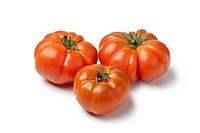 Organic Coeur de Boeuf tomatoes on white background