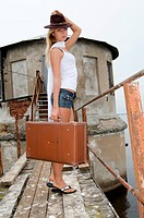 The beautiful young woman with a suitcase at a pier
