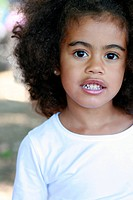 Outdoor portrait of a young mixed race little girl looking at the camera.