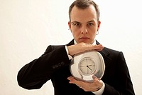 Young businessman holding a clock.