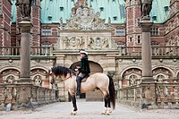 Frederiksborger. Dun stallion with rider in historic costume standing in front of Frederiksborg Palace, Danmark
