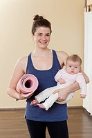 Caucasian mother holding baby in yoga studio
