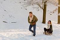 Caucasian man pulling girlfriend on sled in snow