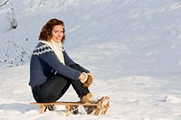 Caucasian woman sitting on sled in snow