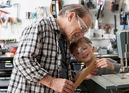 Caucasian man and grandson working in woodshop