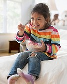 Hispanic girl eating cereal on sofa