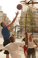 Men playing basketball on court