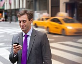 Businessman using cell phone on city street