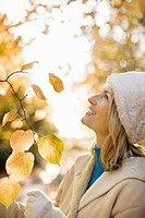 Woman examining autumn leaves in park