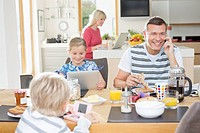 Family using technology at breakfast