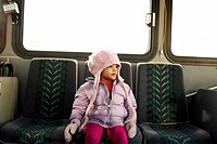 Mixed race girl in hat and gloves riding bus