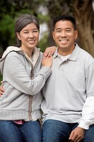 Asian couple smiling together outdoors