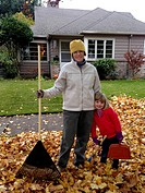 Caucasian mother and daughter raking autumn leaves