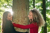 Teenage girls hugging tree in forest