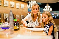 Mother and daughter eating at restaurant
