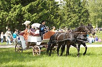 People in old wear ride in the carriage