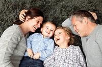 Family smiling together on carpet
