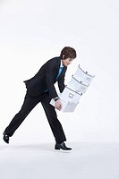 a man in business suit holding a pile of boxes