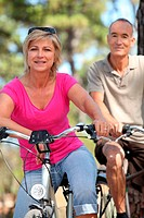 60 years old man and woman doing bike