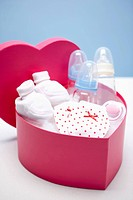 a pink heart box filled with baby items