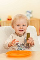 Adorable baby boy eating pickled cucumber.