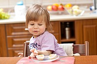Cute two year old girl eating at the dinner table.