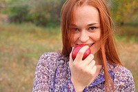 portrait of young woman holding red apple in hand