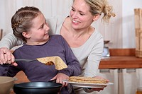 Mother and daughter having fun cooking pancakes