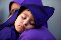 A boy dressed as a penitent sleeps in her father shoulder at the Jesus Nazareno del Perdon procession during Easter Holy Week in Antigua Guatemala, Gu...