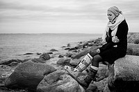 Germany, Kiel, Woman with cast and neck brace sitting on rocks at coast, looking away