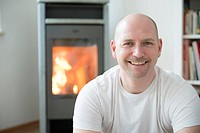 Germany, Munich, Portrait of man in his living room with fireplace, smiling