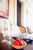 Bowl of strawberries and champagne next to laptop on table